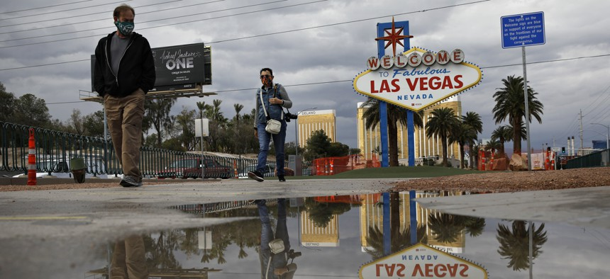 """People wearing face masks visit the usually crowded """"Welcome to Fabulous Las Vegas Nevada"""" sign amid the coronavirus outbreak along the Las Vegas Strip, Tuesday, April 7, 2020, in Las Vegas."""