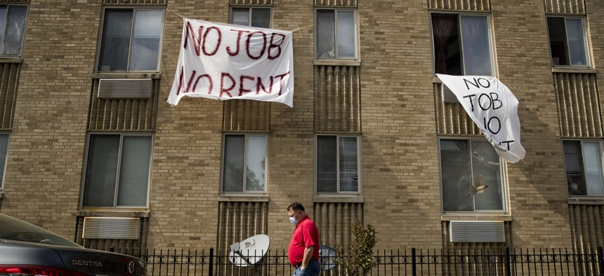 """In this May 20, 2020, file photo, signs that read """"No Job No Rent"""" hang from the windows of an apartment building during the coronavirus pandemic in Northwest Washington."""