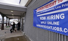 "In this Dec. 10, 2020 file photo, a ""Now Hiring"" sign hangs on the front wall of a Harbor Freight Tools store in Manchester, N.H."