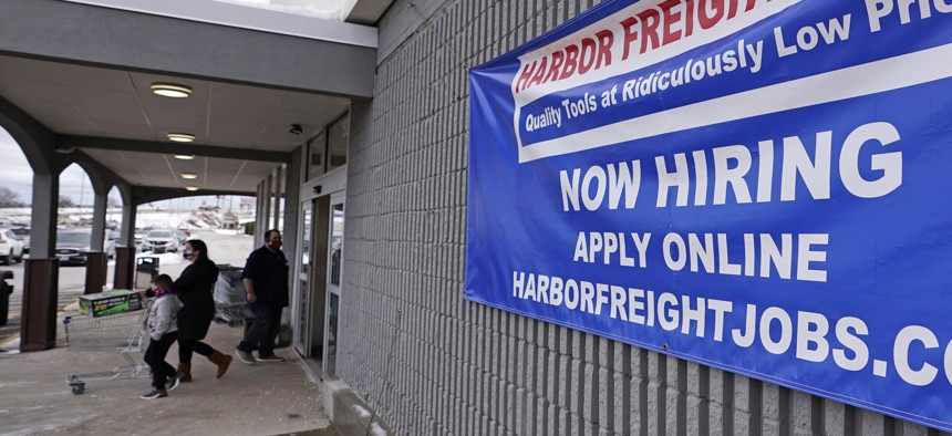 """In this Dec. 10, 2020 file photo, a """"Now Hiring"""" sign hangs on the front wall of a Harbor Freight Tools store in Manchester, N.H."""