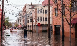 Hoboken, New Jersey, Man standing on the flooded street is talking to someone left in the building, ambulance car in the background.