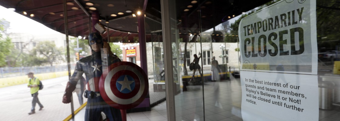 A pedestrian passes a business which has closed temporarily in San Antonio, Tuesday, March 24, 2020. San Antonio, like several other major Texas cities, will begin stay at home orders at the end of the day Tuesday to help battle the effects of the coronavirus.