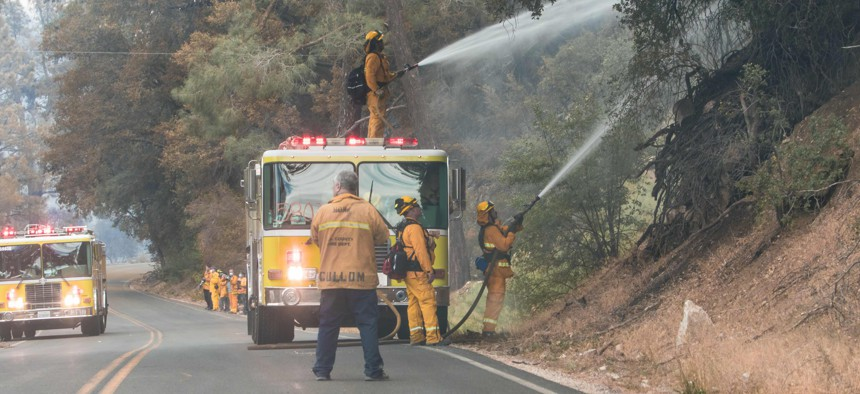 Firefighters clear land and throw water during a wildfire in California.