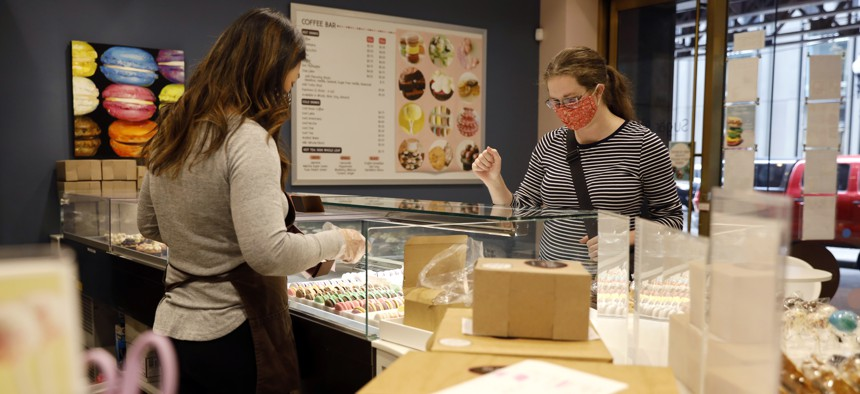 A customer interacts with shop owner Teresa Ging( left) while shopping for bakery goods in Sugar Bliss Bakery in Chicago's famed Loop, Tuesday, May 4, 2021. In many downtown areas where companies closed their offices and commuting ground to a halt, sandwich shops, bakeries and other small businesses are waiting with guarded optimism for their customers to return.