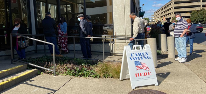 Voters line up outside a polling place Wednesday, Oct. 21, 2020, in Charleston, W.Va.