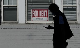 In this Oct. 20, 2020 file photo, a man walks in front of a For Rent sign in a window of a residential property in San Francisco.