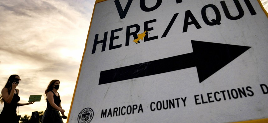 Voters deliver their ballot to a polling station in Tempe, Ariz. Arizona.