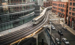 An L train passes over a city street in Chicago.