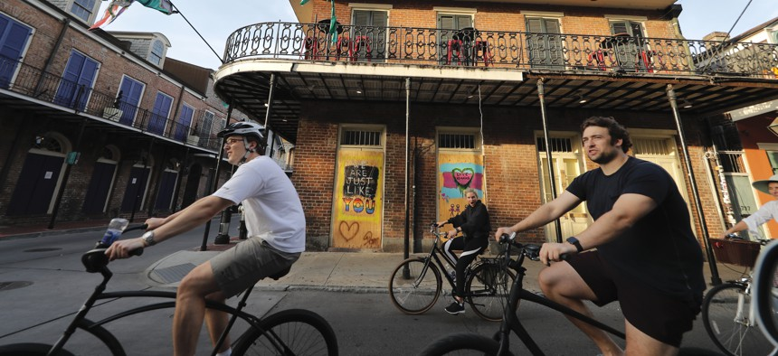 People ride bikes through the largely shuttered French Quarter of New Orleans, Tuesday, May 12, 2020. Attempts to curb the spread of COVID-19 have visited an economic whammy on the state as oil prices have plummeted and tourism has dried up.