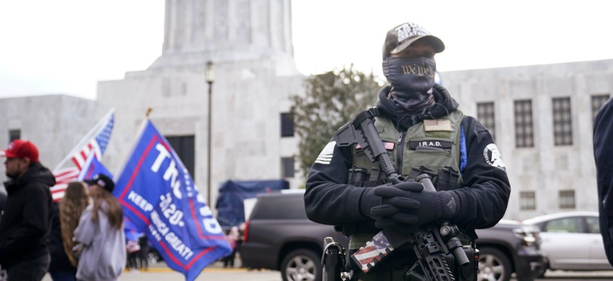 A man holds a gun as he stands in front of the Oregon State Capitol building in Salem, Ore.