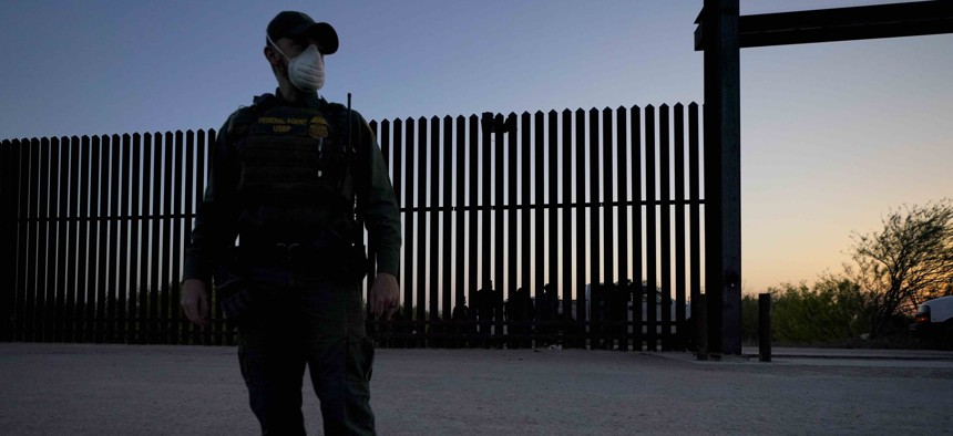 In this March 21, 2021 file photo, a U.S. Customs and Border Protection agent looks on near a gate on the U.S.-Mexico border wall as agents take migrants into custody, in Abram-Perezville, Texas.