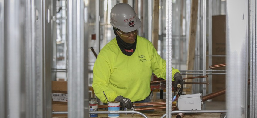 Zakiyyah Askia, a female plumber, welds pipes at a high rise residence under construction in Chicago on Jan. 24, 2019.