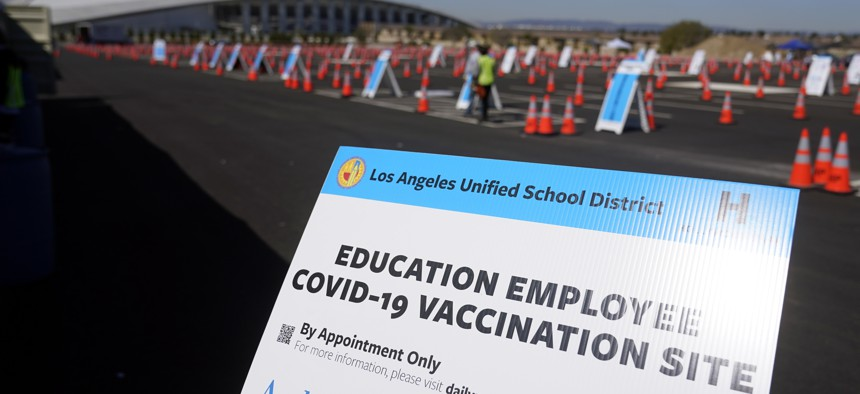 In this March 2, 2021, file photo, a sign is placed at a COVID-19 vaccination site for employees of the Los Angeles school district in the parking lot of SOFI Stadium in Inglewood, Calif.