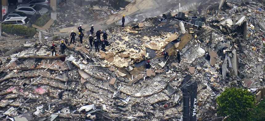 In this June 25, 2021, file photo, rescue workers search in the rubble at the Champlain Towers South Condo in Surfside, Fla.