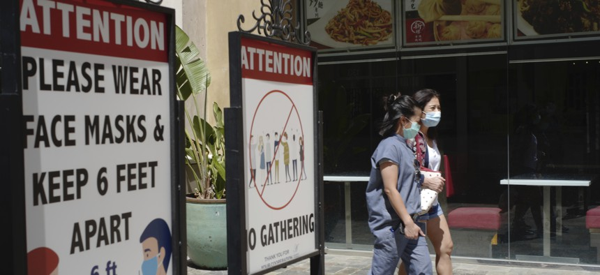 In this June 11, 2021, file photo, customers wear face masks in an outdoor mall with closed business amid the COVID-19 pandemic in Los Angeles. The latest alarming coronavirus variant, the delta variant, is exploiting low global vaccination rates and a rush to ease pandemic restrictions, adding new urgency to the drive to get more shots in arms and slow its supercharged spread.