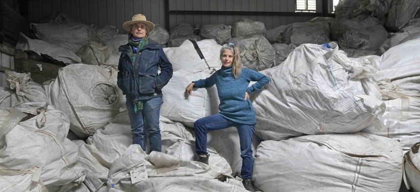 Gail, right, and Amy Hepworth, owners of Hepworth Farms, pose for a picture on bags full of hemp plants at Hepworth Farms in Milton, N.Y., Monday, April 12, 2021.