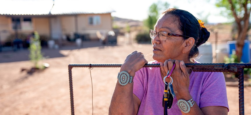 A Navajo woman standing by the gate of her home.