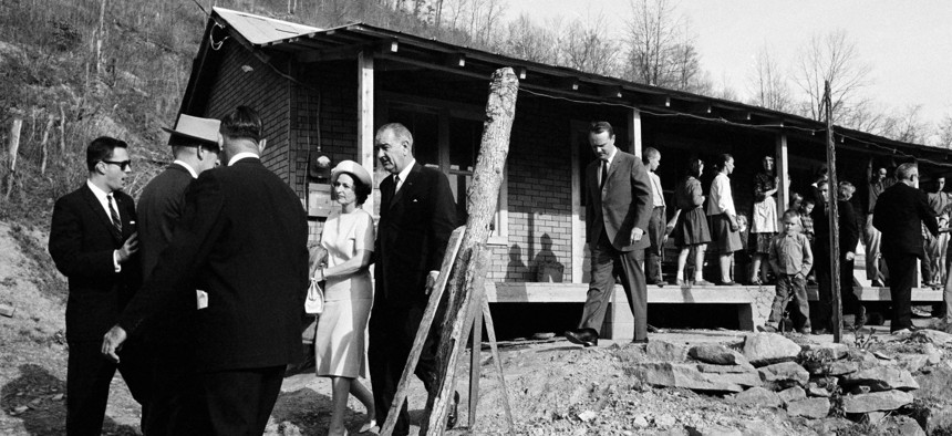 This April 24, 1964, file photo shows President Lyndon Johnson and his wife, Lady Bird, center left, leave the home in Inez, Ky., of Tom Fletcher, a father of eight who told Johnson he'd been out of work for nearly two years.