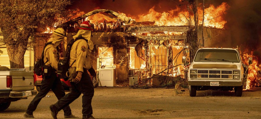 Firefighters pass a burning home as the Sugar Fire, part of the Beckwourth Complex Fire, tears through Doyle, Calif., on Saturday, July 10, 2021.