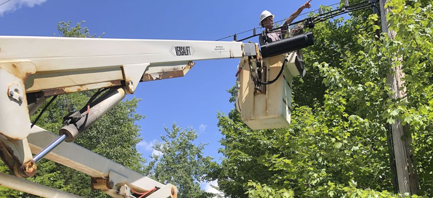 A Consolidated Communications technician works on a line used to provide broadband internet service in a rural area on Wednesday, July 29, 2020, in Stowe, Vt. Vermont officials are working to expand internet service using federal pandemic relief funds.