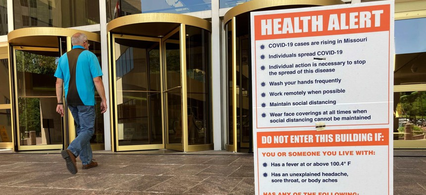A sign warning of COVID-19 dangers remains in place Tuesday, June 15, 2021, outside the entryway of a state office building in Jefferson City, Mo.