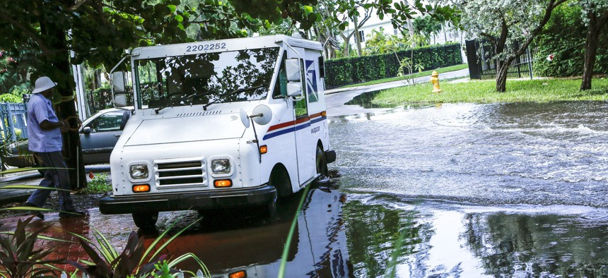In this June 19, 2019 file photo, a postal worker returns to their truck parked on a flooded street in Miami caused by high tides.