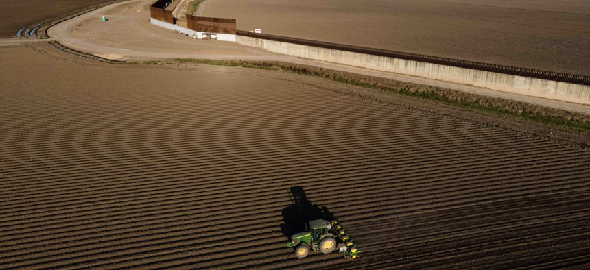In this photo taken by a drone, the border wall construction is seen near farmland as a tractor plows a field, Friday, March 19, 2021, in Progreso, Texas.