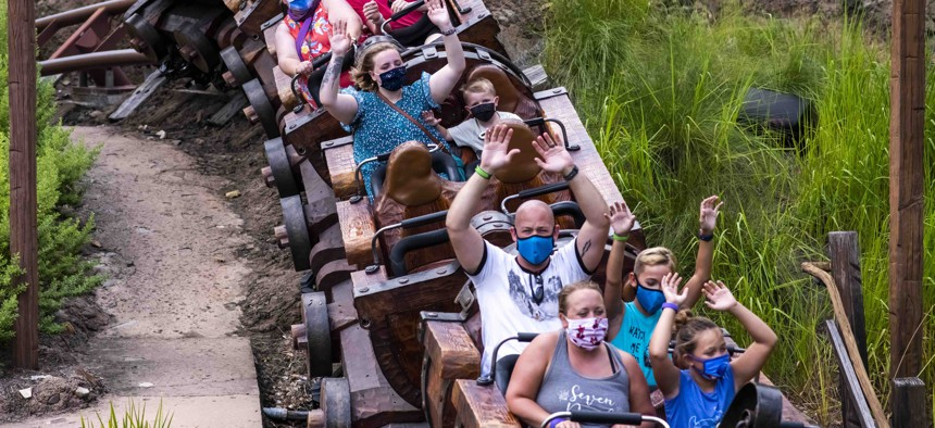 Guests wear face masks due to the Covid-19 pandemic while riding the Seven Dwarfs Mine Train attraction at Walt Disney World Resort's Magic Kingdom on Thursday, August 13, 2020, in Lake Buena Vista, Fla.