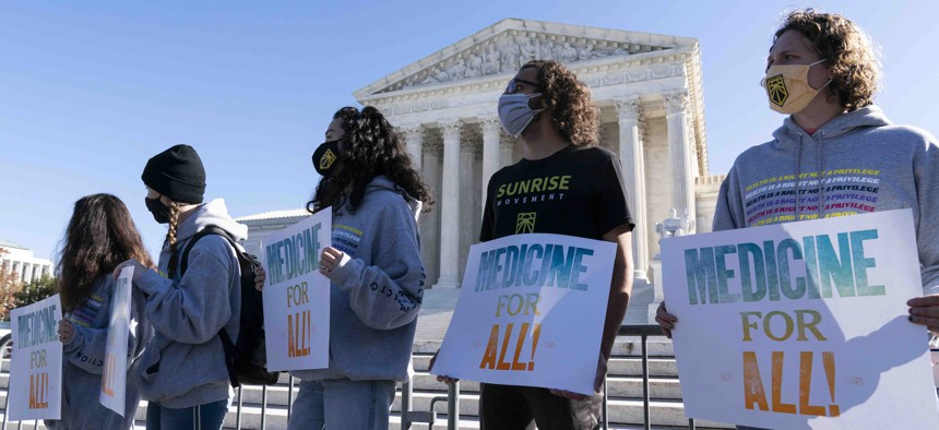 Demonstrators hold signs in front of the U.S. Supreme Court as arguments are heard about the Affordable Care Act Tuesday, Nov. 10, 2020, in Washington.