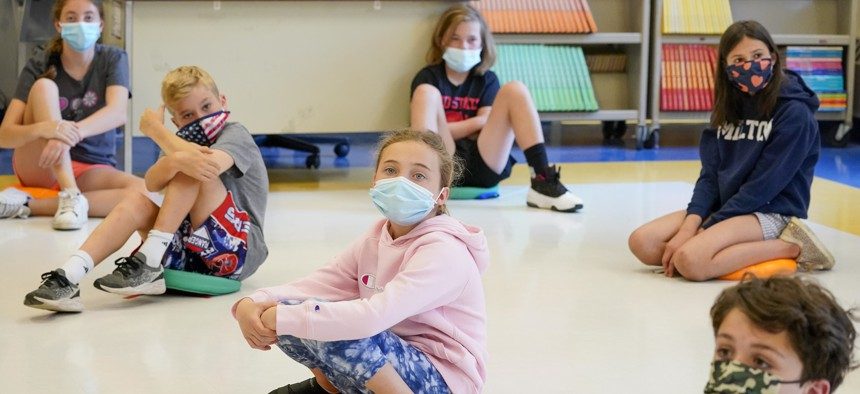 In this May 18, 2021 file photo, fifth graders wearing face masks are seated at proper social distancing during a music class at the Milton Elementary School in Rye, N.Y.