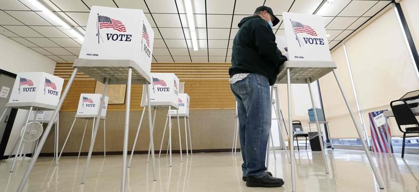 In this Oct. 20, 2020, file photo, Kelly Wingfield, of Urbandale, Iowa, fills out his ballot during early voting for the general election in Adel, Iowa.