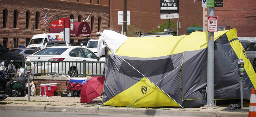 A tent put up by homeless individuals sits on a sidewalk Thursday, July 8, 2021, one block east of the Colorado Convention Center, the site of a major League Baseball promotion to mark the playing of the All Star Game in Denver.