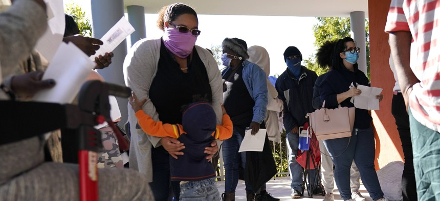 People wait in line to receive a $250 grocery gift card available to Miami residents experiencing hardship and food insecurity due to COVID-19, Tuesday, Dec. 8, 2020, in Miami. The CARES Act provides the funding for the cards.