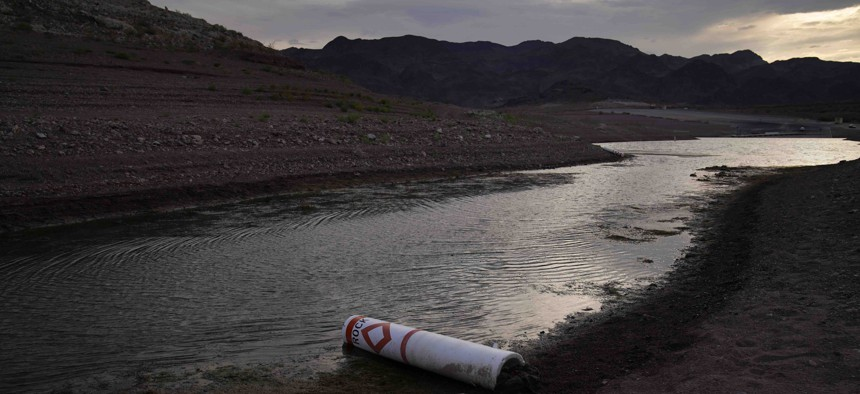 A buoy once used to warn of a submerged rock rests on the ground along the waterline near a closed boat ramp on Lake Mead at the Lake Mead National Recreation Area, Friday, Aug. 13, 2021, near Boulder City, Nev. Water levels at Lake Mead, the largest reservoir on the Colorado River, have fallen to record lows.
