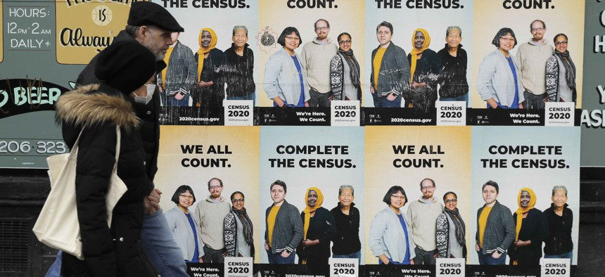 In this Wednesday, April 1, 2020 file photo, People walk past posters encouraging participation in the 2020 Census in Seattle's Capitol Hill neighborhood.
