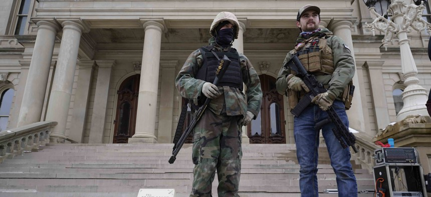 Armed men stand on the steps at the State Capitol after a rally in support of President Donald Trump in Lansing, Mich., Wednesday, Jan. 6, 2021.