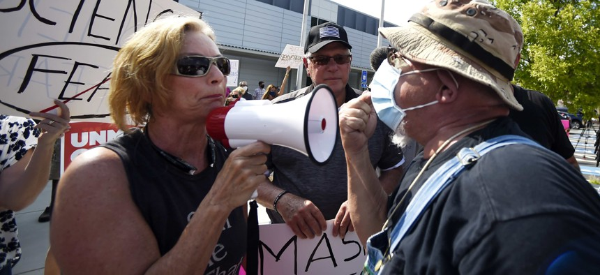 A pro-mask demonstrator, right, speaks with a non-mask demonstrator, left at the Cobb County School Board Headquarters during a pro mask wearing protest, Thursday, Aug. 12, 2021, in Marietta, Ga.