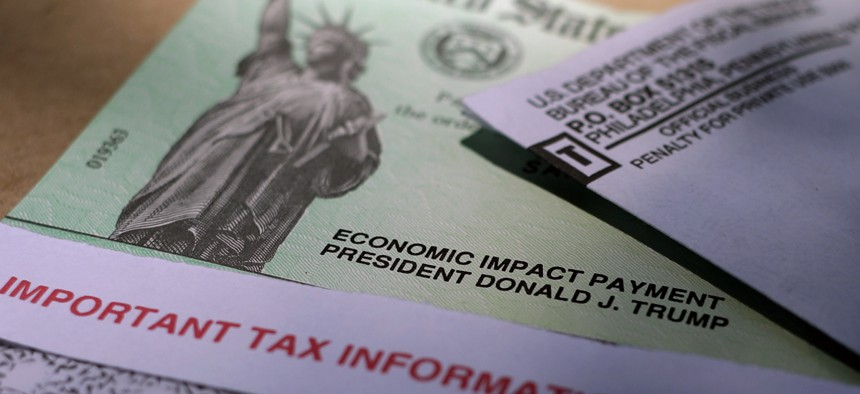 In this April 23, 2020 file photo, President Donald J. Trump's name is printed on a stimulus check issued by the IRS. Later rounds of the payments helped boost personal income in 2021.