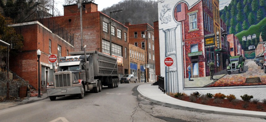 In this Feb. 9, 2011, file photo, a coal truck drives out of downtown Welch, W.Va. The Economic Development Administration makes grants to help struggling communities.