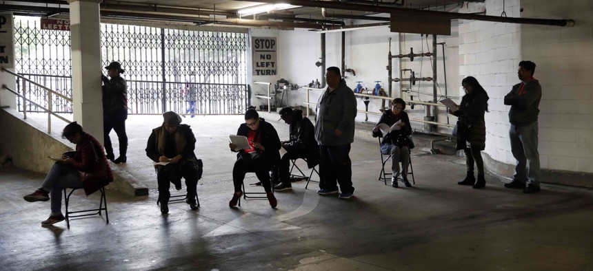 In this March 13, 2020, file photo, unionized hospitality workers wait in line in a basement garage to apply for unemployment benefits at the Hospitality Training Academy in Los Angeles.