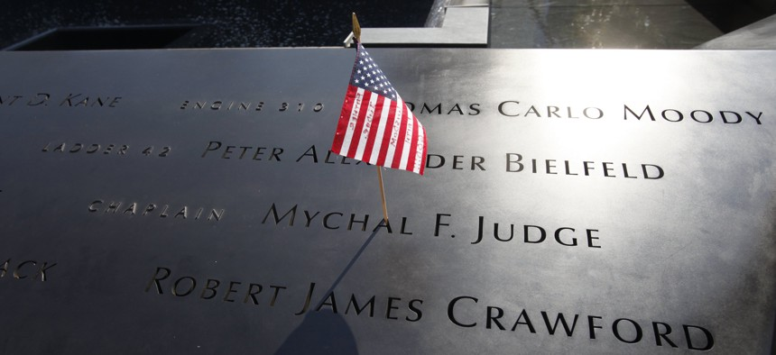 In this Monday, Sept. 12, 2011 file photo, a U.S. flag is stuck into the etched name of Father Mychal F. Judge, the New York Fire Department chaplain who died in the 9/11 attacks on the World Trade Center, at the National September 11 Memorial in New York.