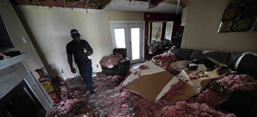 Michael Lathers walks past the collapsed ceiling in his flooded home in the aftermath of Hurricane Ida in LaPlace, La., Tuesday, Sept. 7, 2021.