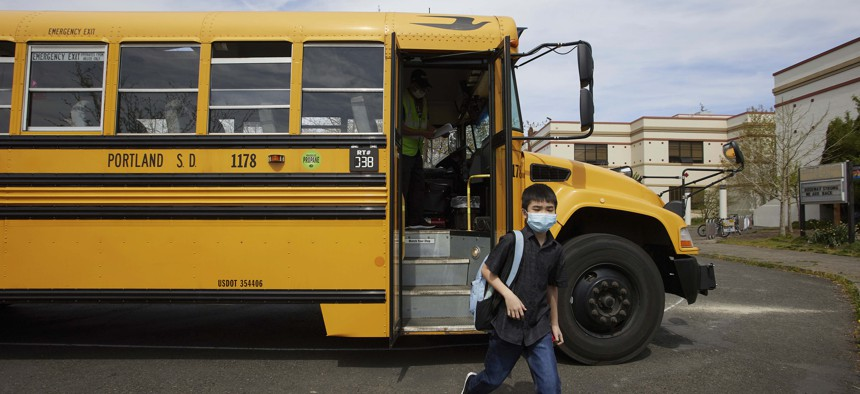 A student gets off the bus at Roseway Heights Middle School on the first day of in-person hybrid learning on Monday, Apr. 19, 2021 in Portland, Ore.