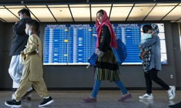 Families evacuated from Kabul, Afghanistan, walk through the terminal before boarding a bus after they arrived at Washington Dulles International Airport, in Chantilly, Va., on Friday, Sept. 3, 2021.