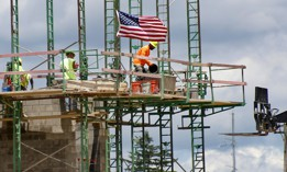 Workers on scaffolding lay blocks on one of the larger buildings at a development site where various residential units and commercial sites are under construction, Thursday, June 11, 2020, in Cranberry Township, Butler County, Pa.