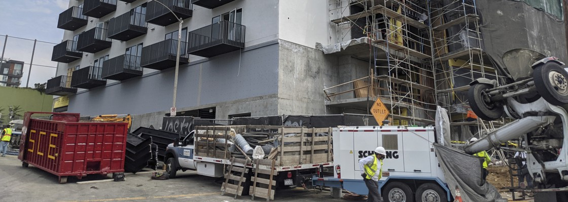 In this June 18, 2021, photo, construction workers finish the exterior of an apartment building downtown Los Angeles.