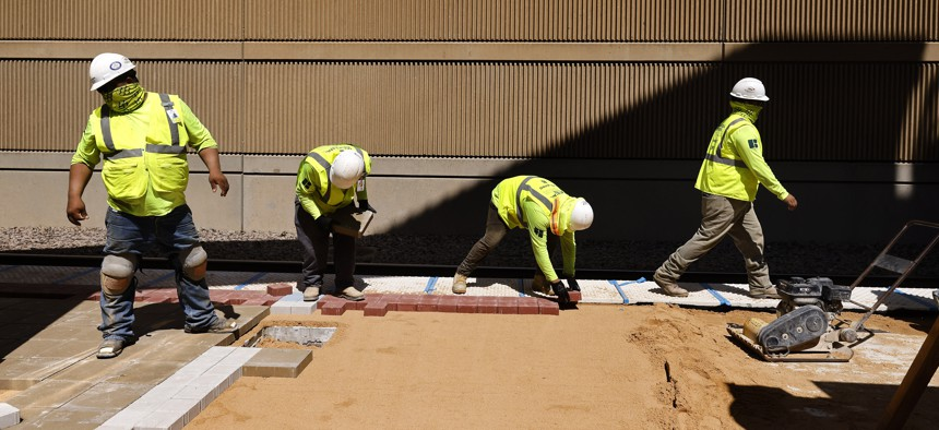 Construction workers remake the platform at DART's Mockingbird Station during U.S. Transportation Secretary Pete Buttigieg's visit to Dallas, Wednesday, Aug. 11, 2021. Buttigieg toured some of Dallas' transportation sites to see and hear how the bipartisan infrastructure deal's investment in jobs, airports and transit will benefit the area.