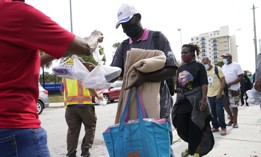 Residents stand in line for prepared meals during a food distribution held by the Overtown Youth Center and other local organizations, Monday, April 12, 2021, in the Overtown neighborhood in Miami.