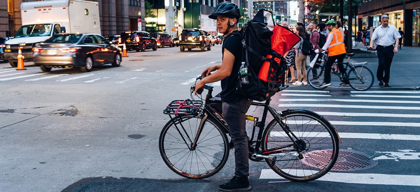 Hispanic courier on bicycle in crosswalk in New York City