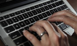 In this June 19, 2017, file photo, a person types on a laptop keyboard in North Andover, Mass.